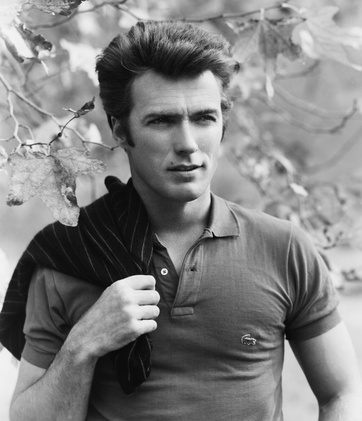 circa 1960:  Portrait of American actor and director Clint Eastwood squinting while posing under a tree, with a sweater slung over his shoulder. Eastwood wears a Lacoste polo T-shirt.  (Photo by Hulton Archive/Getty Images)