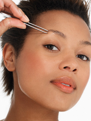 Young Woman Tweezing Eyebrows --- Image by © Royalty-Free/Corbis
