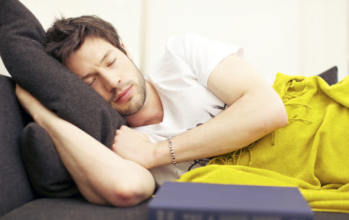 Young Asian man in a deep exhausted sleep after studying from his book.