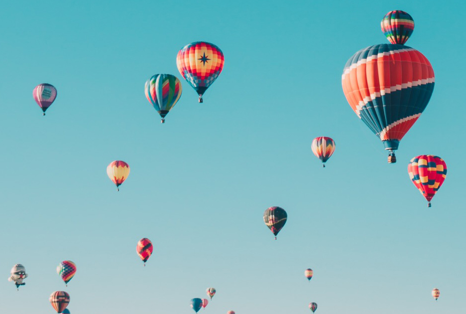colourful hot air balloons floating in a blue sky