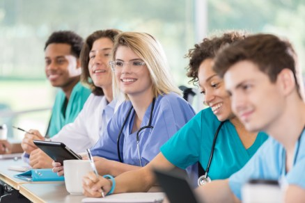A diverse group of attentive male and female pre-med or nursing students attend class. They are wearing scrubs and lab coats.