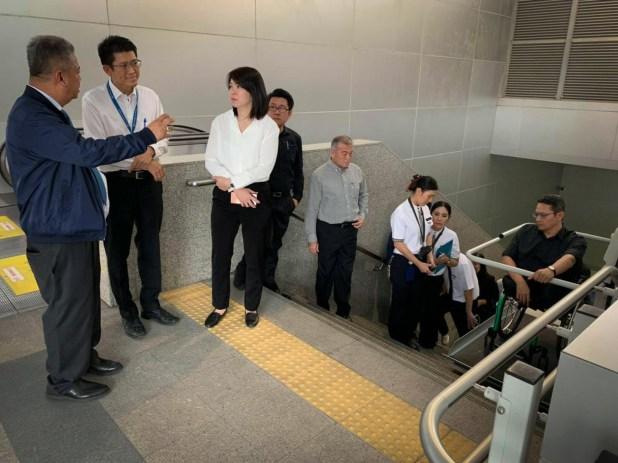 [ภาพอาจารย์สุภรธรรมกำลังนั่งอยู่บนลิฟท์เกาะราวบันได ลิฟท์ค้าง]