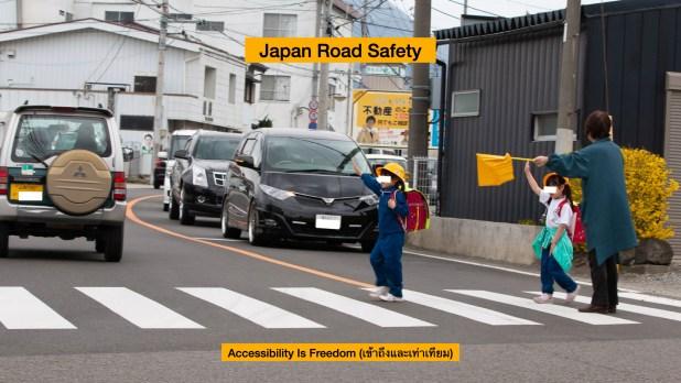 ภาพ นักเรียนตัวน้อยๆ กำลังยกมือเป็นสัญญาณข้ามถนน มี จนท กำลังโบกธงให้