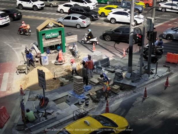 ภาพ จากมุมบน คนงานกำลังก่อสร้างทางเท้าใหม่