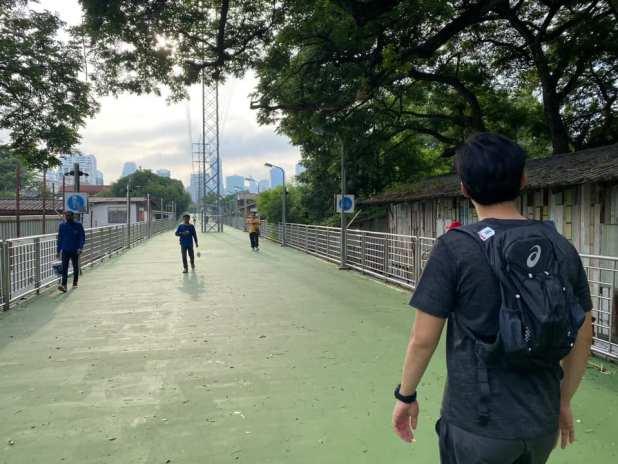 ภาพ คุณเอิร์ธ กำลังเดินบนสะพานเขียว