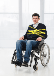 young disabled man in wheelchair with caution tape