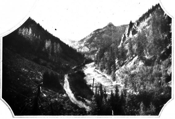 A typical stretch of road along the new highway running through the Gallatin Valley near Bozeman, Montana. The Geysers-to-Glaciers trail is guided by the main range of the Rocky Mountains, winding in and out through picturesque gulches. over crashing mountain streams, and climbing the easy grades to height, as great as 7500 feet.