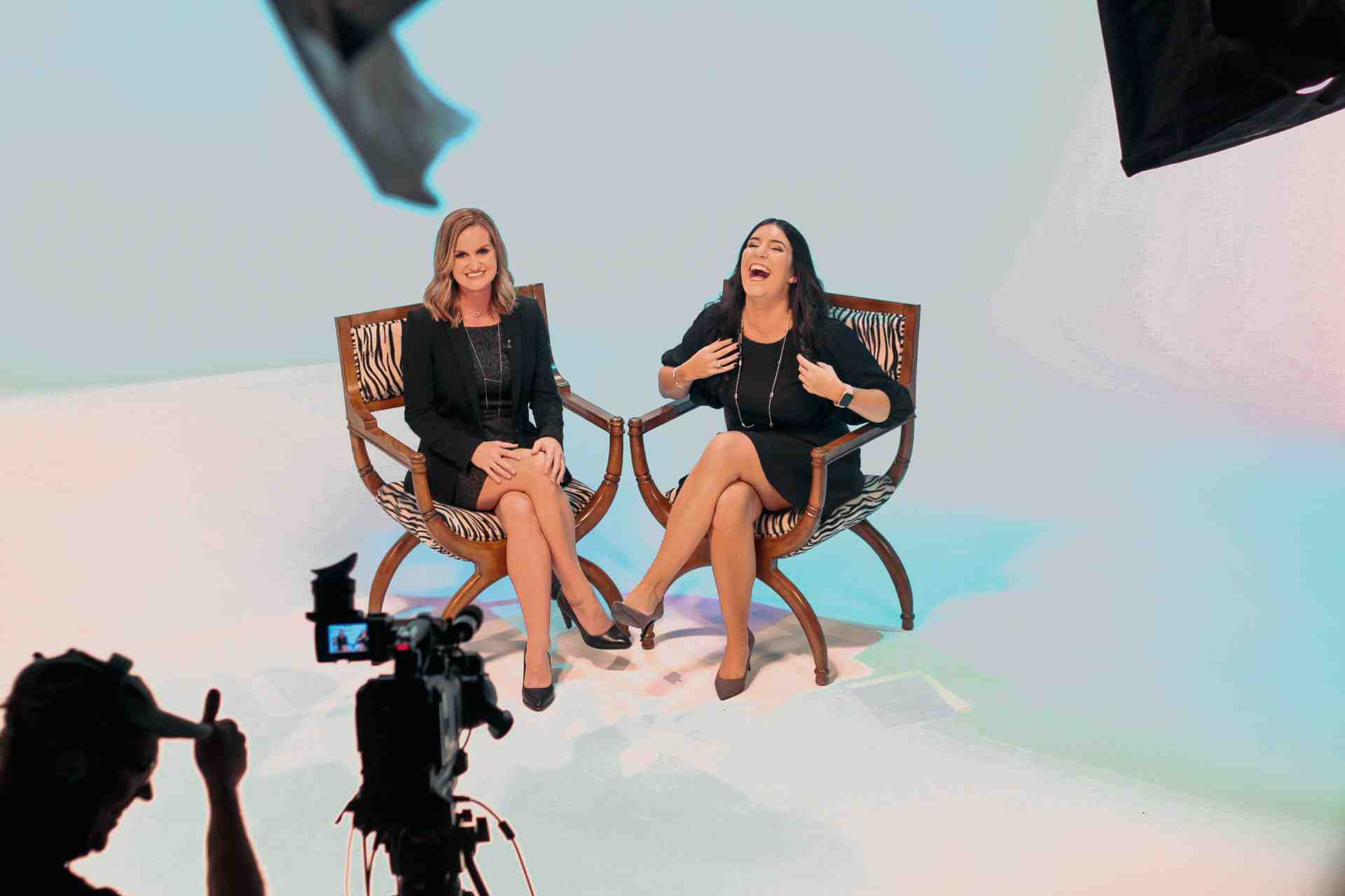 Two women in studio laughing during video shoot