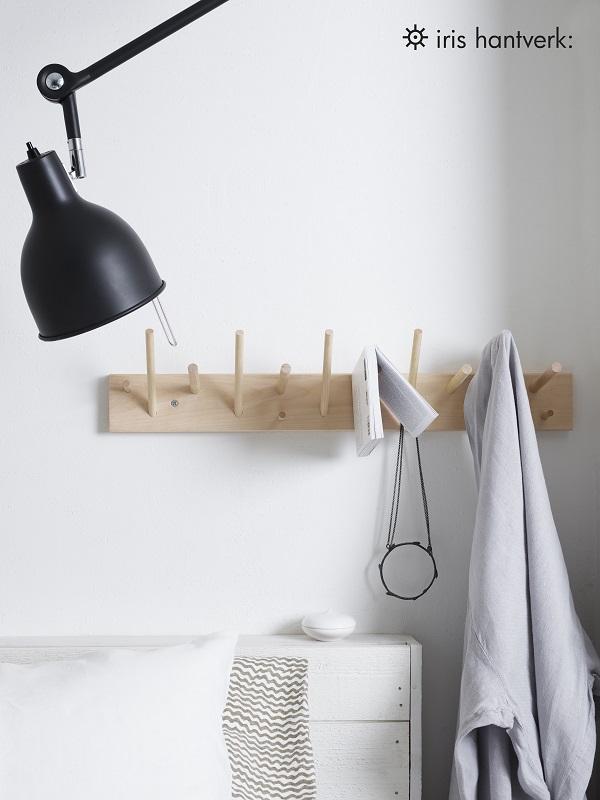 Witte muur met houten rekje in slaapkamer - via Accessorize your Home