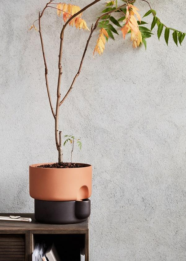 Tweekleurige zelfwaterende bloempot van terracotta op een houten tafel - via Accessorize your Home