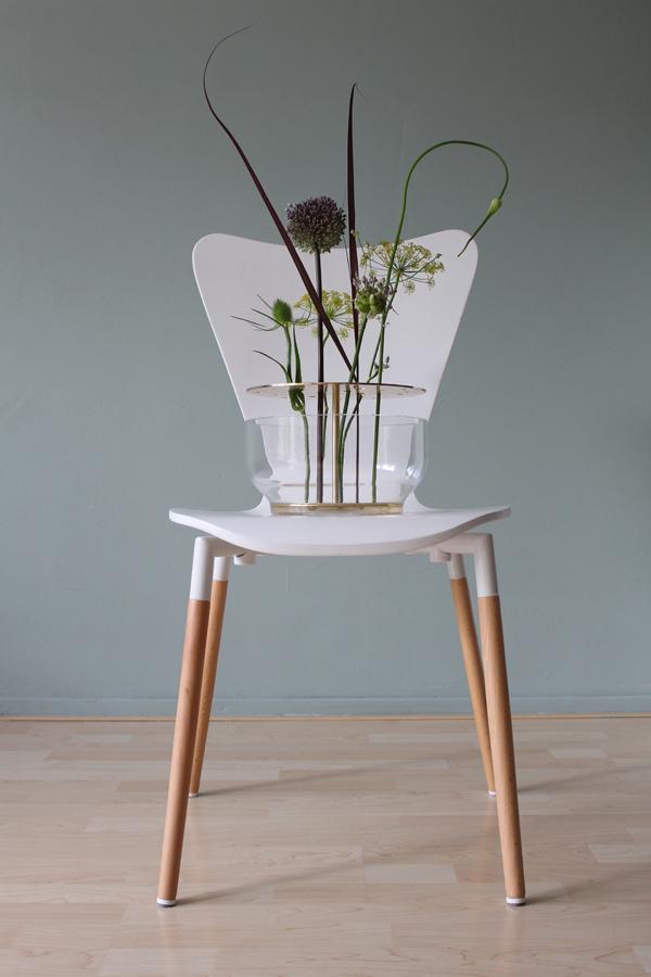 Ikebana vaas met wilde bloemen op een witte stoel tegen een groene muur - via Accessorize your Home