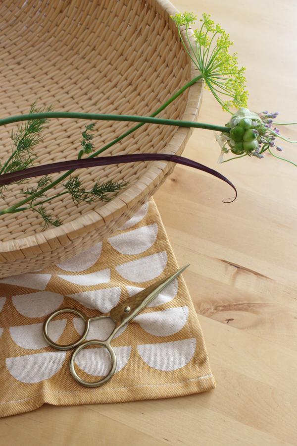 Rieten mand met bloemen op houten tafel met theedoek Bridges van Ferm Living en messing schaar - via Accessorize your Home