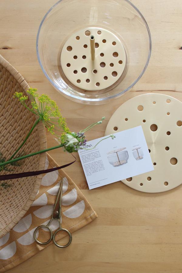 Ikebana vaas op een houten tafel met rieten mand met bloemen en theedoek van Ferm Living - via Accessorize your Home