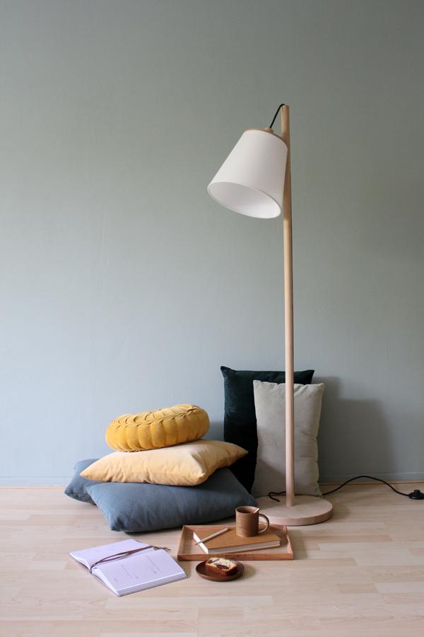 Stapel fluwelen kussens op lichthouten vloer met koffie en cake en een Scandinavische vloerlamp - via Accessorize your Home