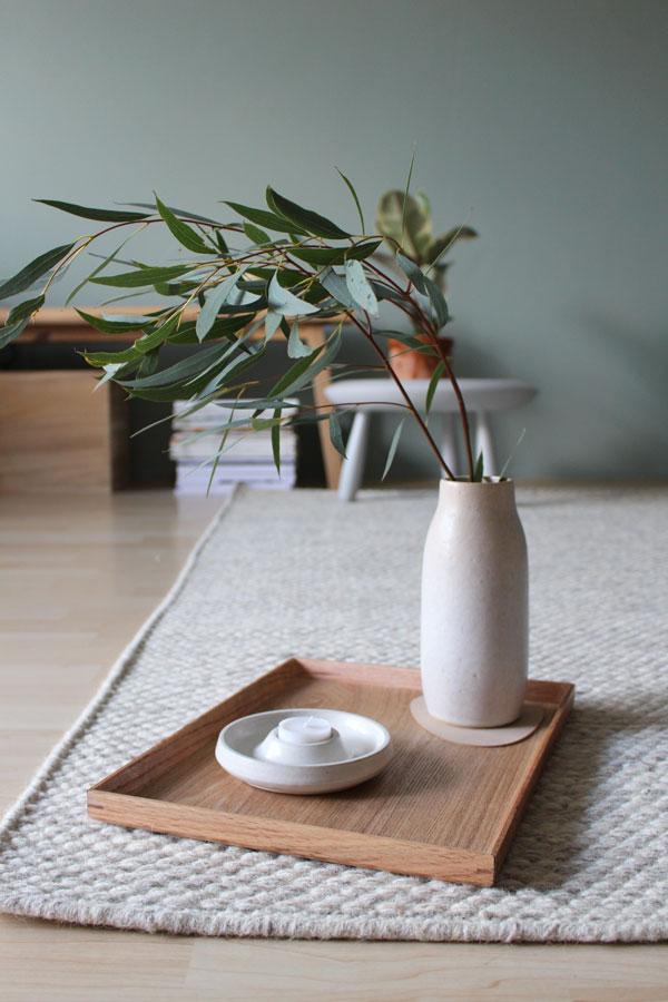 Wollen vloerkleed met houten dienblad met vaas met eucalyptus - via Accessorize your Home