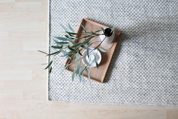 Wollen vloerkleed op lichte vloer met houten dienblad met witte vaas met eucalyptus - via Accessorize your Home