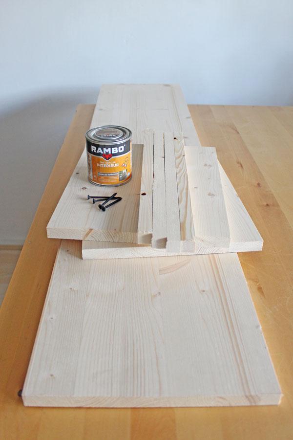 Benodigdheden voor het maken van een zwevende wandplank: planken van geschaafd vuren, mat zwarte schroeven en houtlak - via Accessorize your Home