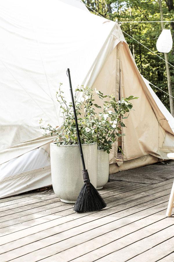 Houten dek met grote potten gevuld met planten en een zwarte bezem gemaakt van bamboe en diverse grassoorten.