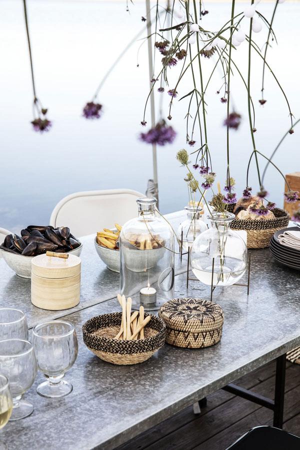 Feestelijk gedekte eettafel gedekt met mooie schalen gevuld met mosselen, glazen vazen en hangende verbena.