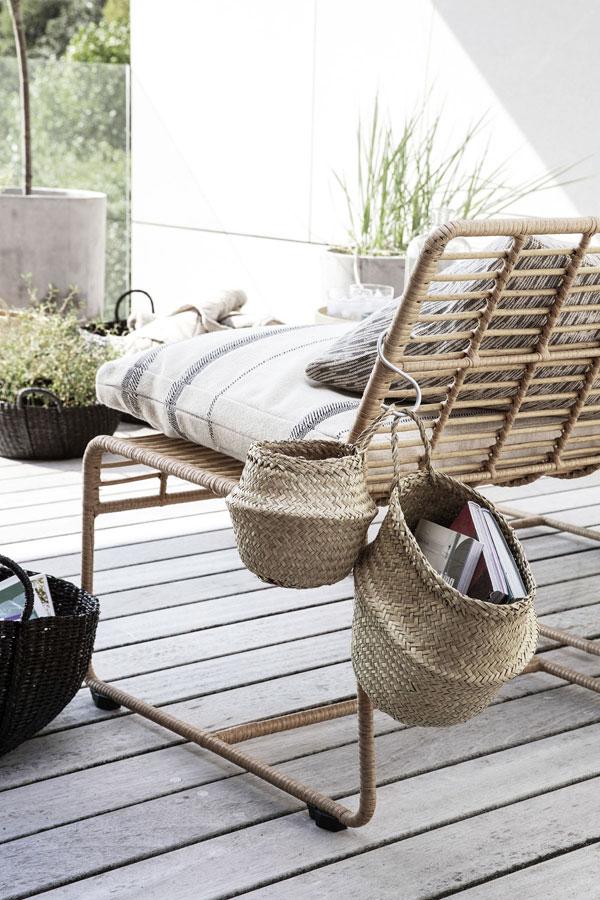 Naturel loungestoel van House Doctor op zonnig terras met katoenen kussens met streeppatroon en enkele manden die aan de stoel gehangen zijn waar boeken inzitten.