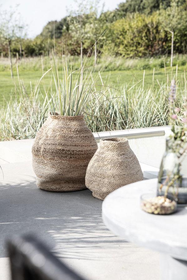 Organisch gevormde rotan manden op een zonovergoten terras omringt met grassoorten.