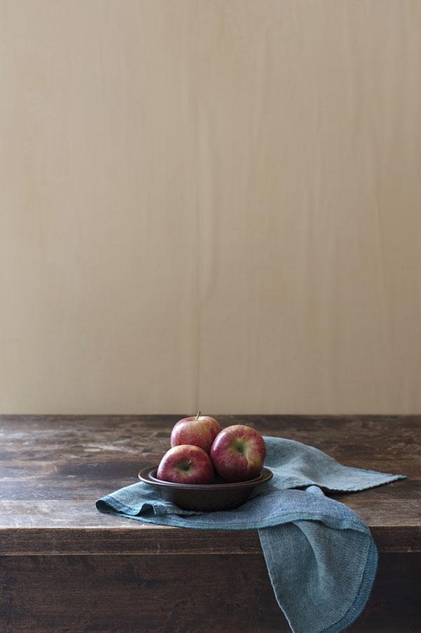 Theedoek in twee aardetinten met bord met appels op houten tafel - via Accessorize your Home