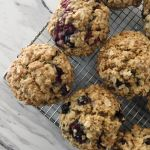 Raspberry oatmeal spelt muffins cooling on a metal rack on a white marbled countertop