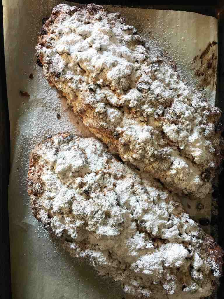 Two loaves of german christmas stollen dusted with icing sugar