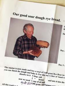 An older man holding two loaves of no knead sourdough rye bread