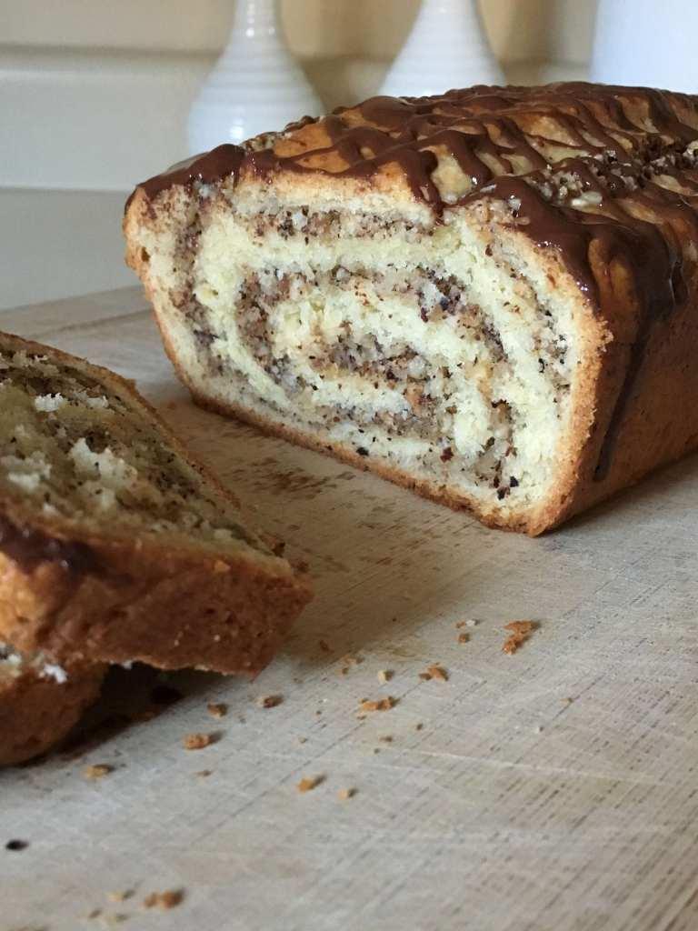 Close up of the hazelnut swirls in a chocolate hazelnut swirl spelt bread sitting on a wooden cutting board