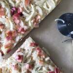 Slices of spelt flammkuchen with pizza blade