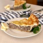 Two slices of Traditional Tourtiere Pie with Flaky Spelt Pie Crust on white plates with a sprig of parsley and two pieces of cheddar cheese.