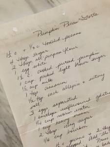 Handwritten recipe for a Pumpkin Pecan Torte on a plain piece of paper sitting on a white marble countertop