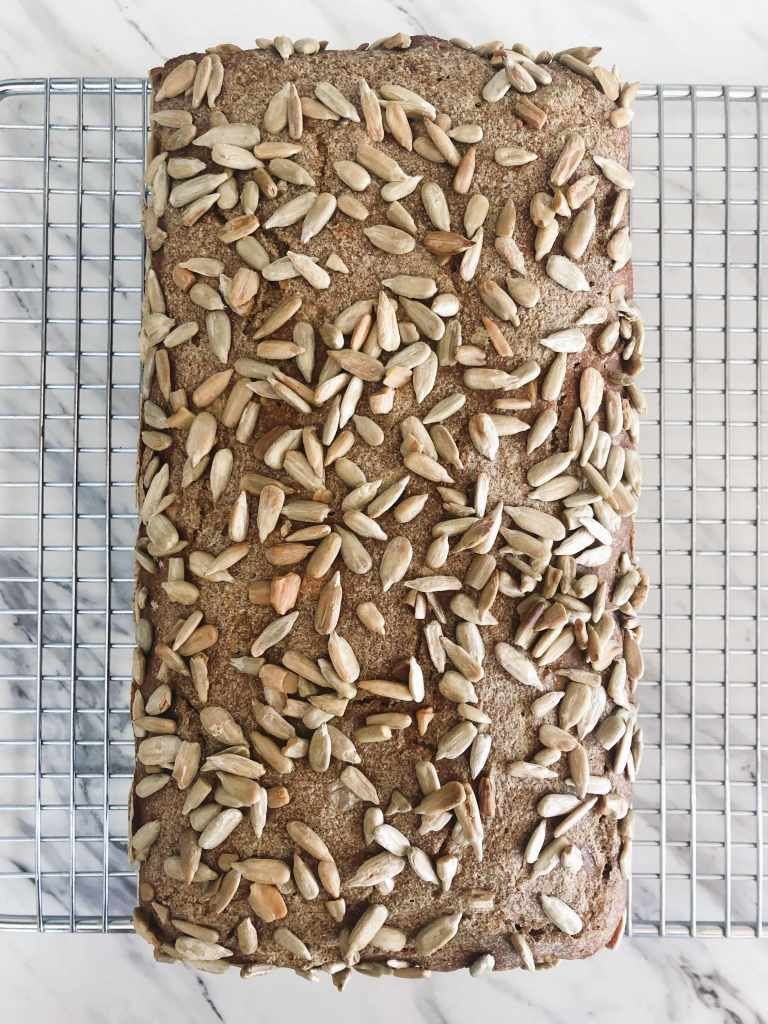 One loaf of whole grain rye sourdough bread with sunflower seeds on top on a cooling rack