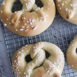 Two sweet pretzels made from yeast dough cooling on a wire rack after being baked to a golden brown