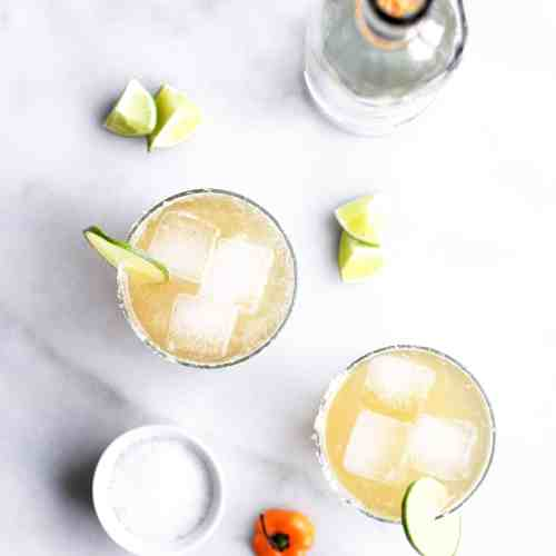 Spicy habanero ginger beer margaritas in glasses with ice, lime and salt