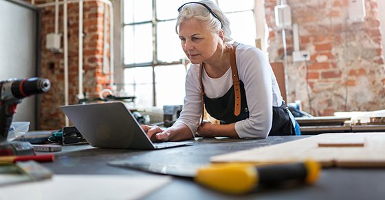 Older Woman on Laptop Researching on Buying vs Leasing Equipment for Her Business