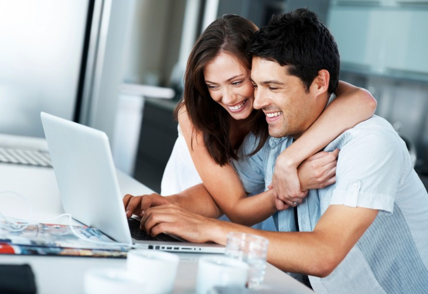 Portrait of a smiling young couple surfing internet on laptop in kitchen at home