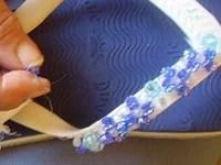 Coloque o nylon  na agulha e as pedras na seguinte seqüência: uma pedra azul clara (costure), 4 pedras azuis escuras (costure cruzando as pedras), na parte de cima, coloque a pedra transparente