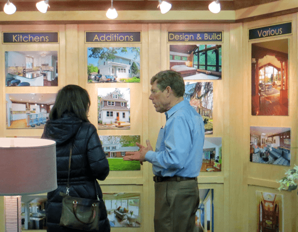 photo of Jim Acheson with Guest at Acheson Builders booth of the Home, Garden, and Lifestyle Show in Ann Arbor 2015