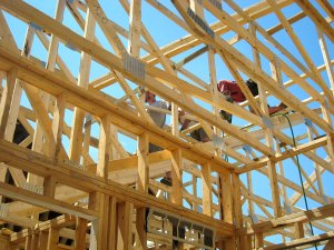 photo of Acheson Builders crew members up in roof section fastening framing pieces during reconstruction of house in Dexter, Michigan