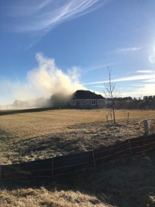 photo of smoke rising out of suburban house in Dexter, Michigan prior to restoration by Acheson Builders