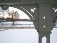 photo of fancy scroll-cut wooden post of front porch in winter with snow blanketing front yard