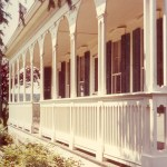 photo of white painted ornate long front porch covering full width of large country house