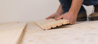 Handyman installing wooden floor in new house