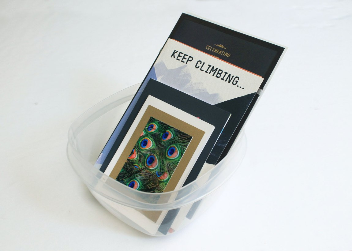 Repurpose plastic containers to store cards or mementos