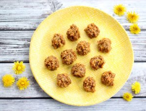 Carrot Cake Energy Balls on a yellow plate with dandelion flowers around it