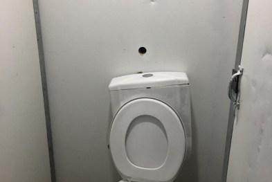 Homem é detido após abrir buraco em parede e filmar mulheres em banheiro de festa