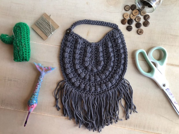Follow this free crochet pattern and learn how to make this trendy, crochet boho baby bib. It's perfect for selling in your Etsy shop or gifting to mamas to be.