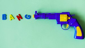 toy pistol with the word bang in toy letters by muzzle